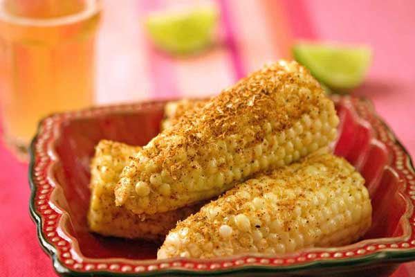 Elotes are coated in a creamy chili sauce.